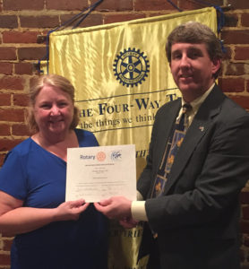 Club Treasurer, Peter Strickland, presents the District's award for successfully completing a District Grant for Buddy Backpacks to club president, Karen Kratz.