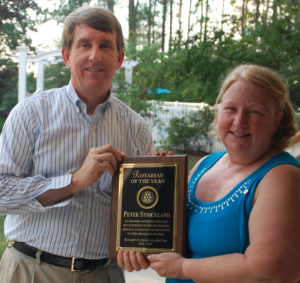 President Karen Kratz presents Peter Strickland with the Rotarian of the Year award.